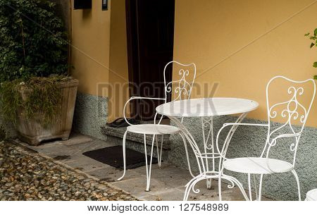 two white metal chairs and a coffee table outside a small cafe in Italy