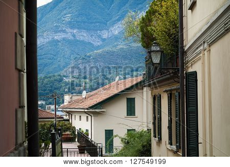 a quaint narrow street in Bellagio (North Italy) with sunlit mountains visible in the background