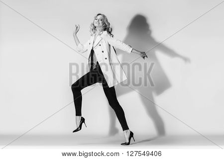 The emotional fashion-model running in black leggings on a white background. Studio shot.