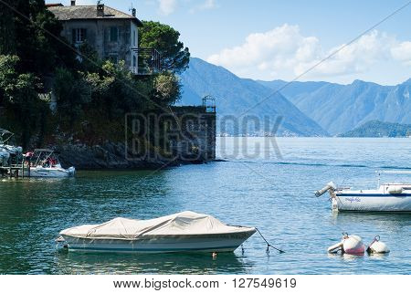 Varenna, Italy - September 4th 2015: people embarking on a boat in Varenna (Lake Como Italy) with more white boats in the foreground.