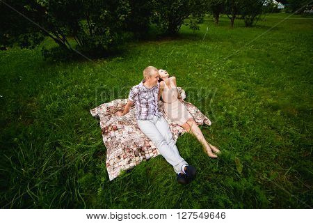 holidays vacation love and friendship concept - smiling couple lying on blanket and looking at each other in park