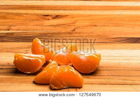 A tangerine peeled and pulled apart on a teak cutting board