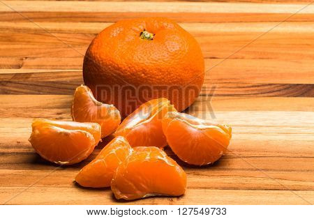 A whole tangerine and pieces parted on a teak cutting board