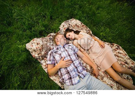 holidays vacation love and friendship concept - smiling couple lying on blanket and looking at each other in park. Top view