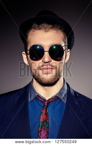 Close-up portrait of a stylish young man wearing black round sunglasses. Optics style. Fashion studio shot.
