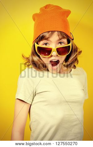 Portrait of a funny expressive teen girl over yellow background.