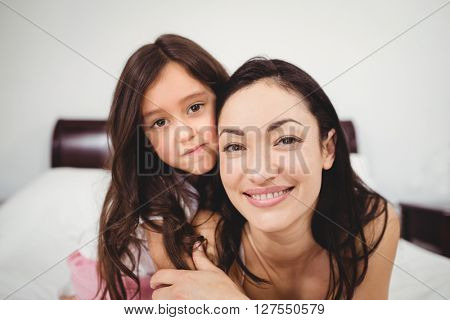 Close-up portrait of happy mother and daughter on bed at home