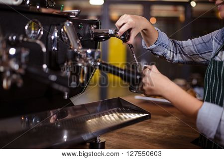 Smiling barista making hot milk with coffee machine at the bar