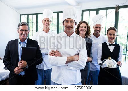 Portrait of happy restaurant team standing together in restaurant