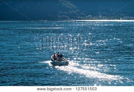 Abbadia Lariana Italy - September 6th 2015: three men riding a motor boat at Lake Como Lombardy Italy.