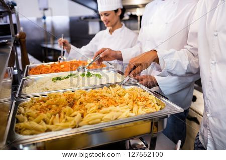 Chefs standing at serving trays of pasta in commercial kitchen