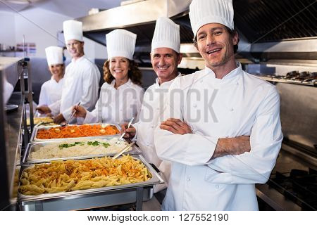Portrait of chefs standing at serving trays of pasta in commercial kitchen