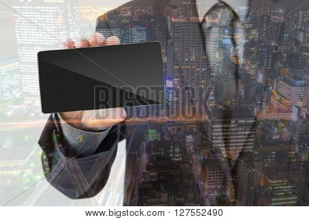 Double exposure of Business man Hand holding mobile smart phone with cityscape