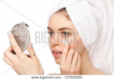 Beautiful young woman applying a creme on her face looking at mirror isolated on white background