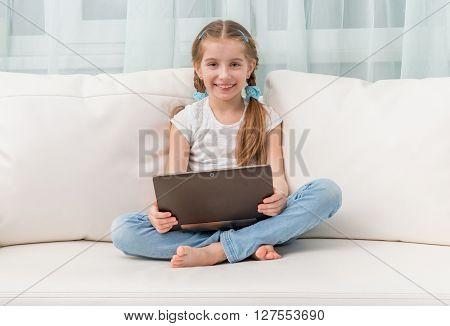 little girl holding notebook on her crossed legs on sofa