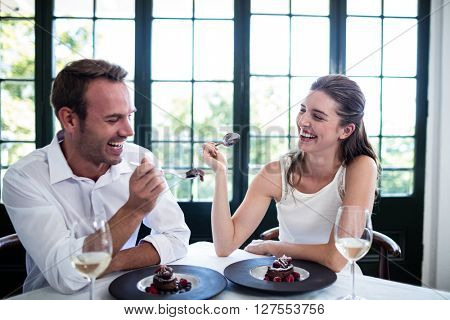 Couple feeding each other and smiling while spending time at the restaurant