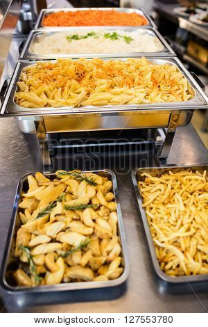 Serving dishes of potato and pasta in commercial kitchen