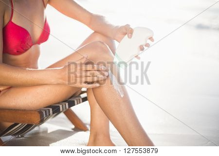 Mid-section of woman sitting on armchair and applying sunscreen lotion on the beach