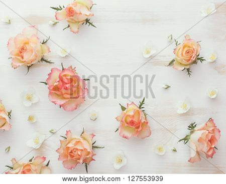 Roses and jasmine natural flower background. Various soft roses and and jasmine flowers scattered on a vintage background, overhead view, vintage toned image