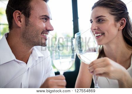 Couple toasting wine glasses at dining table in a restaurant
