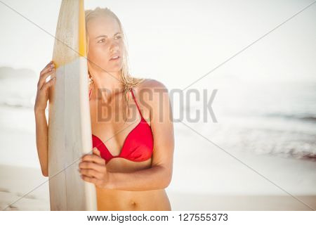 Woman in bikini standing with a surfboard on the beach on a sunny day