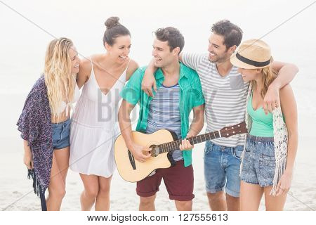 Group of friends standing on the beach with a guitar on a sunny day