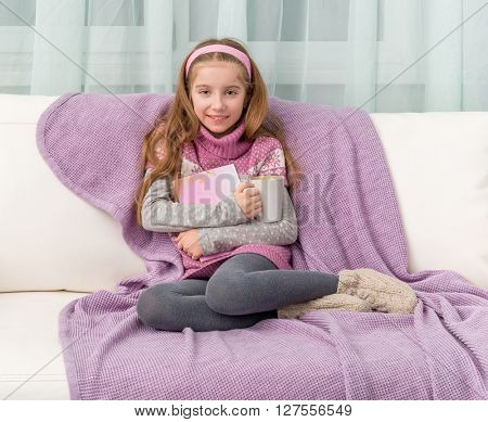 little cute girl on sofa with the book