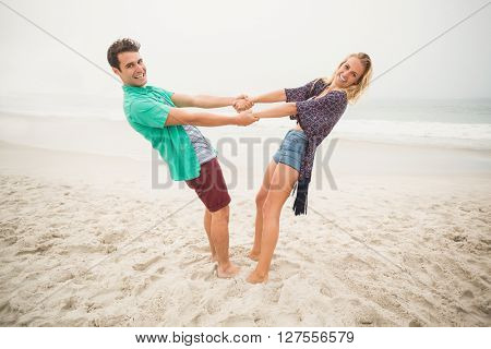 Portrait of happy couple holding hands and bending backwards on the beach