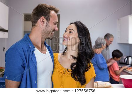 Happy young man and young woman standing in kitchen looking face to face