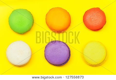 Six colored tasty macarons, sweet meringue-based confection at yellow background, top view