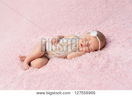 cute smiling newborn baby in wreath sleeps on blanket