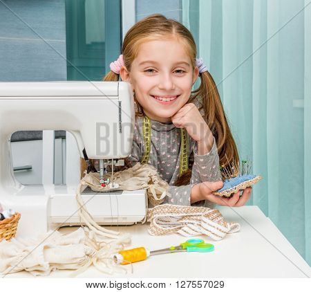 smiling little girl with pincushion in her hands at the table with sewing machine