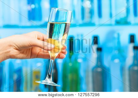 Woman hand toasting champagne in crystal glass at the blue lighting of the bar