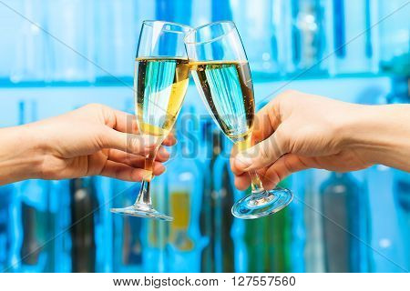Man and woman hands with glasses of champagne at the bar