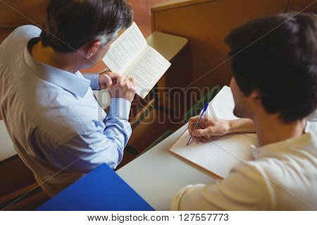 Professor assisting a student with his study in classroom