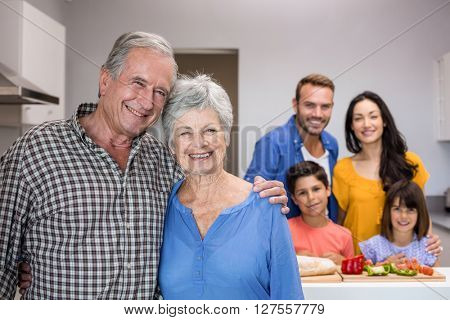Portrait of elderly man and woman in the kitchen and other family member standing in background