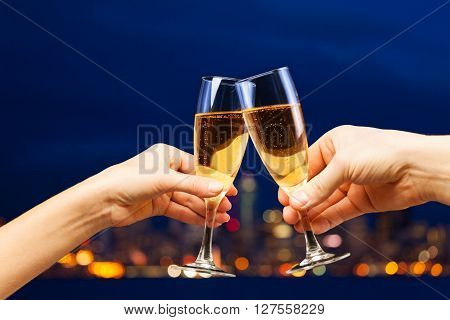 Man and woman hands with champagne glasses toasting against the romantic view of night city illumination