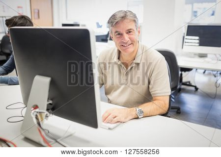 Portrait of happy professor working on computer in classroom