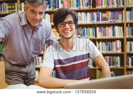 Portrait of smiling student with professor in college library