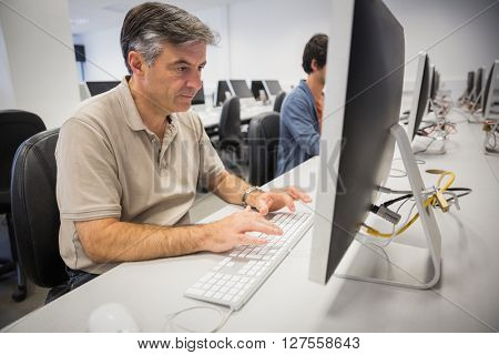 Professor using computer in classroom