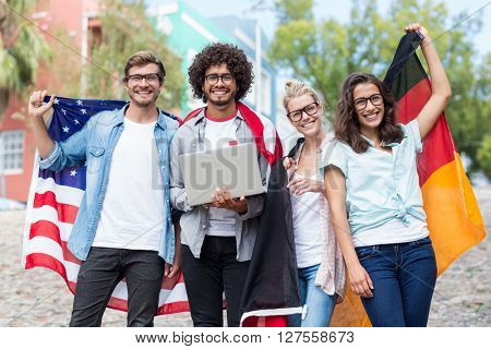 Group of happy friends holding national flag and using laptop