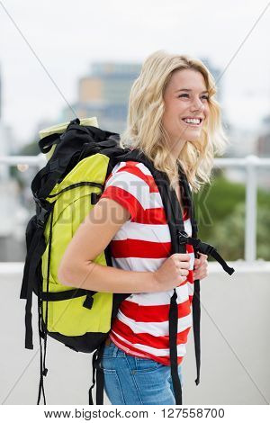 Happy young woman carrying backpack on terrace