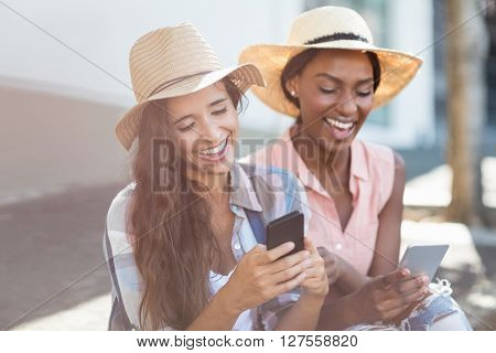 Young women having fun while text messaging on mobile phone