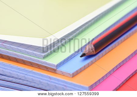 Colorful exercise books and single pencil, back to school concept