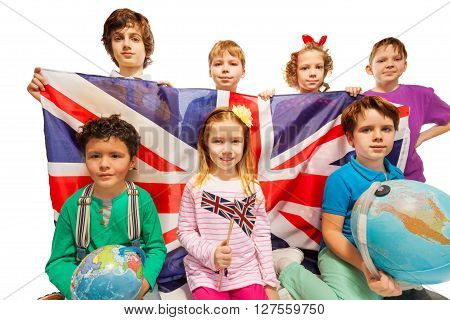Seven happy English kids studying geography with globes and holding flag of Great Britain, isolated on white background