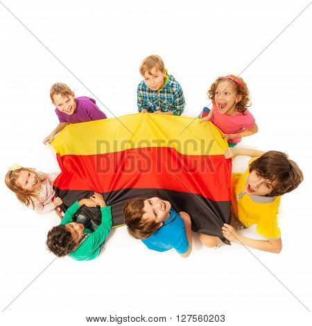 Top view of seven happy kids holding German flag sitting around it, isolated on white background