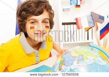 Portrait of smiling German schoolboy learning geography at the light classroom