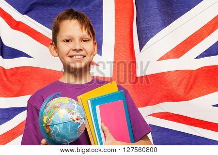 Smiling English student with small globe and textbooks standing against the flag of Great Britain