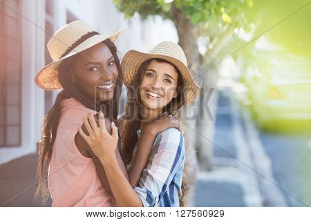 Portrait of friends in hat embracing each other