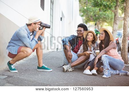Man taking photo of his friends on roadside